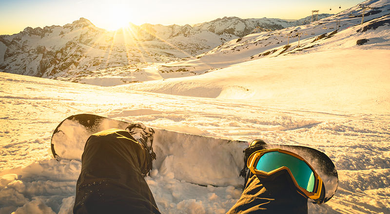 Snowboarder sitting on relax moment at sunset in french alps ski resort