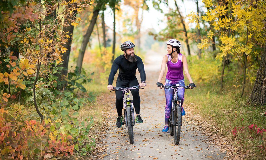 couple cycling on paved trail