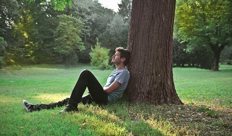 guy sitting by tree