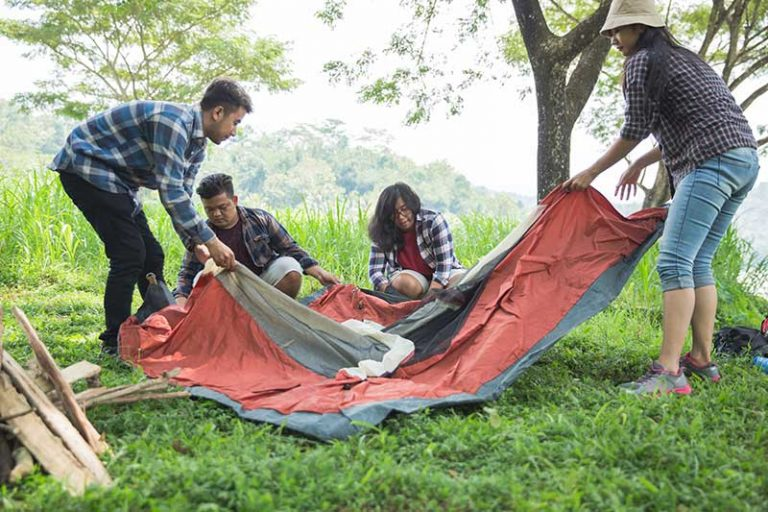 friends breaking down a tent