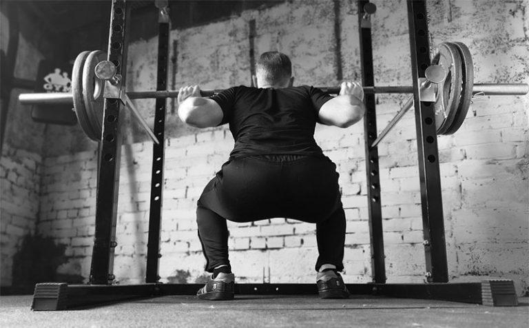 man using squat rack