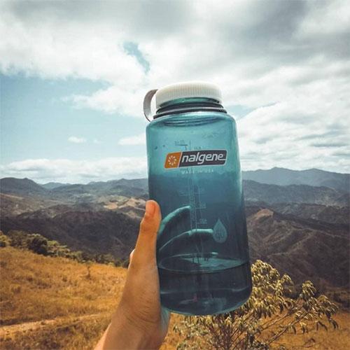 hiker holding up Nalgene water bottle