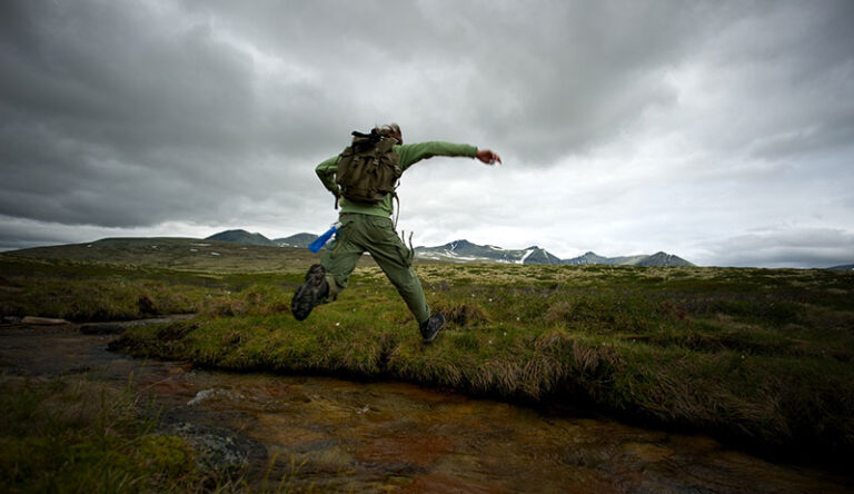 hiker jumping water