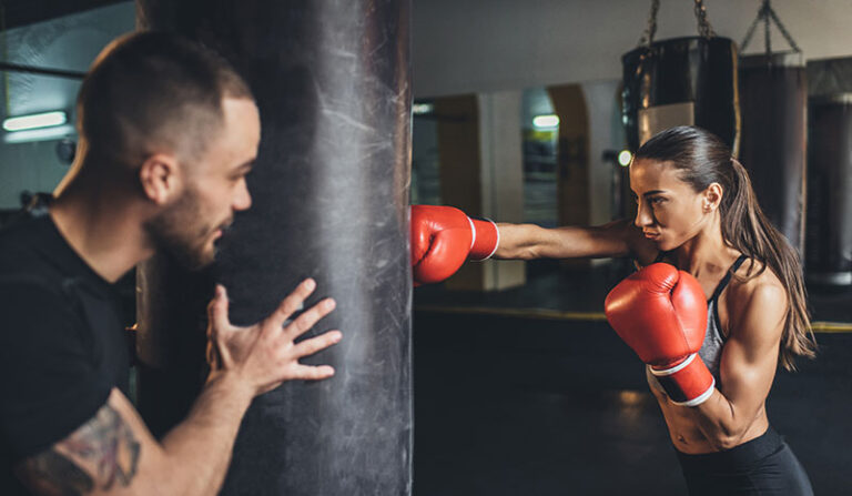 woman punching bag with trainer