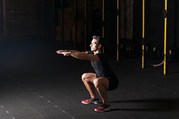 guy doing air squats at gym
