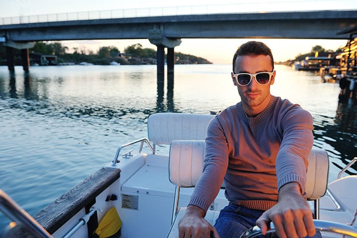 guy in sunglasses driving boat