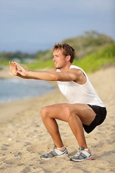man doing air squats