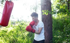 guy boxing punching bag tree