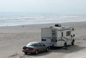 rv pulling car at beach