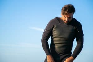 guy putting on wetsuit